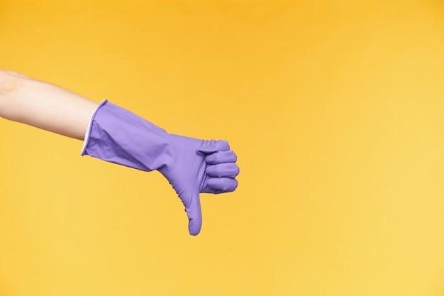 Studiofoto van een lichte, opgeheven hand die met de duim naar beneden wijst terwijl hij negatieve emoties uitdrukt, afkeer toont terwijl hij poseert op gele achtergrond