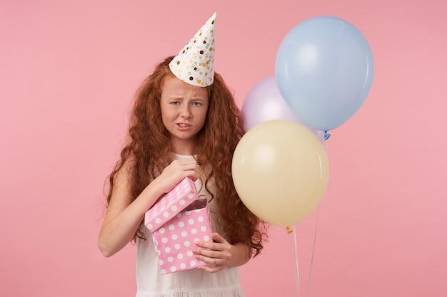 Studiofoto van een vrolijk meisje met rood krullend haar dat een geschenkverpakte doos over roze achtergrond houdt, een witte jurk en een verjaardagspet draagt, helaas in de camera kijkt, in een slechte geest is