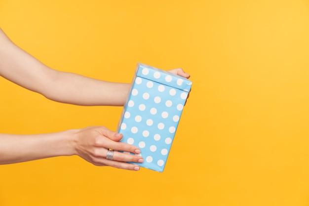 Studiofoto van elegante vrouwelijke handen, lichte handen die worden opgeheven terwijl ze een doos met een cadeautje vasthouden, iemand feliciteren met een verjaardag, geïsoleerd op gele achtergrond