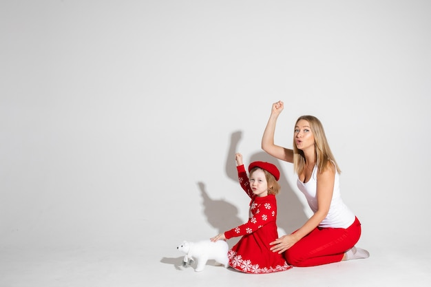 Studiofoto van grappige moeder en dochter in rood en wit poseren met arm omhoog met vuist die een treinfluit imiteren. wit berenstuk speelgoed voor het kind. kopieer ruimte.