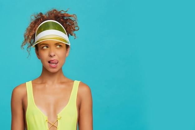Studiofoto van jonge bezorgde roodharige vrouw die haar tong toont terwijl ze verwonderd omhoog kijkt, gekleed in gele zwemkleding terwijl ze zich voordeed op blauwe achtergrond