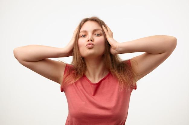 Studiofoto van jonge blonde dame met losse lange haren die haar lippen in luchtkus vouwen en hoofd met opgeheven handen vasthouden terwijl zij op witte achtergrond staat