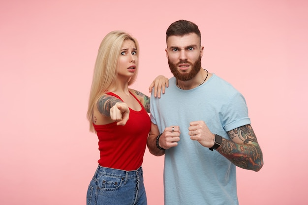 Studiofoto van jonge knappe brunette man die boos zijn vuist opheft terwijl hij zijn overstuur mooie langharige getatoeëerde blonde vriendin gaat beschermen, geïsoleerd over roze achtergrond