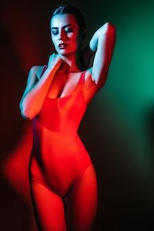 Studiofoto van jonge vrouw op groene en rode achtergrond