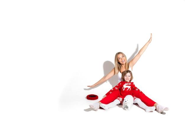 Studiofoto van joviale moeder met uitgestrekte armen met dochter voor haar zittend op de vloer.