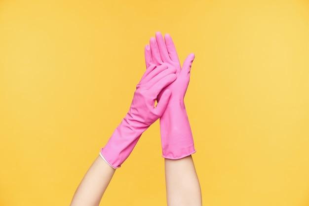 Studiofoto van opgeheven twee handen die elkaar aanraken terwijl het aanbrengen van zeep erop alvorens het te wassen, geïsoleerd over oranje achtergrond. menselijke handen concept