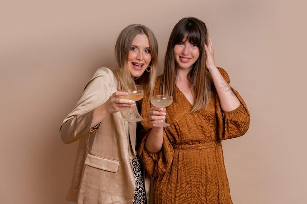 Studiofoto van twee elegante vrouwen in stijlvolle herfstautfit poseren met een glas champagne over een beige muur