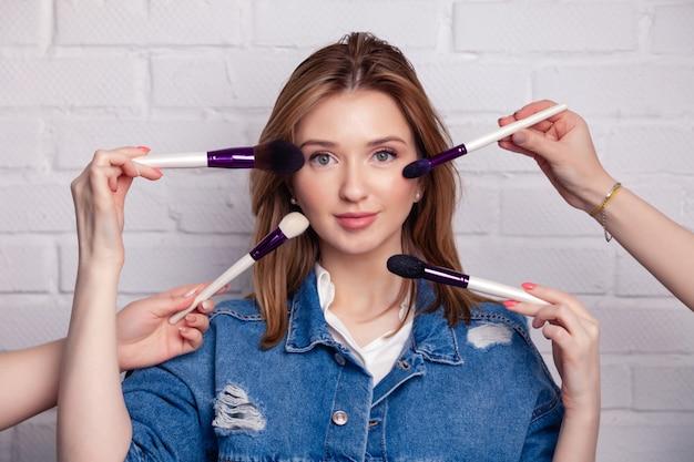 Studiofoto van vele handen met borstels die make-upproces doen aan jonge kaukasische mooie vrouw.