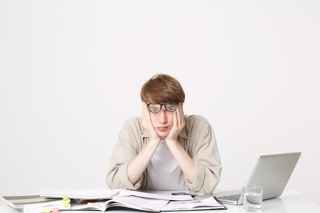 Studiofoto van vermoeide studentenzitting met zijn ellebogen op zijn bureau dat zijn hoofd vasthoudt
