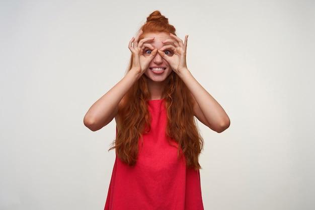 Studiofoto van vrolijke jonge vrouw die haar foxyhaar in knoop draagt, belachelijke gezichten op witte achtergrond maakt, brillen met haar handen maakt en tong toont. positieve emotie gezichtsuitdrukking