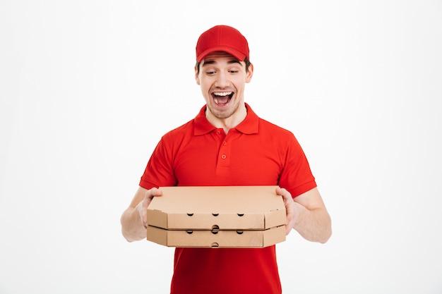 Studiofoto van vrolijke kerel van de bezorgdienst in rode t-shirt en glb die voedselorde geven en twee pizzadozen houden, die over witte ruimte wordt geïsoleerd