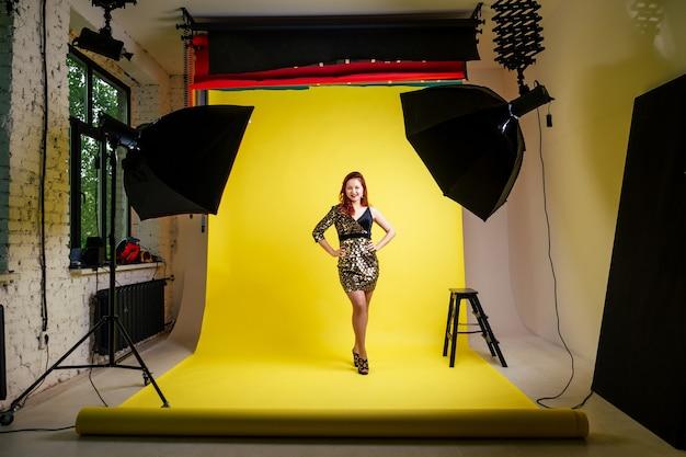 Studiofotosessie van een meisje in een zwarte jurk op een gele achtergrond