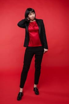 Studioportret van aantrekkelijke glimlachende onderneemster die elegant zwart kostuum met broeken en oxfordschoenen draagt. ze houdt armen gevouwen tegen een rode achtergrond.