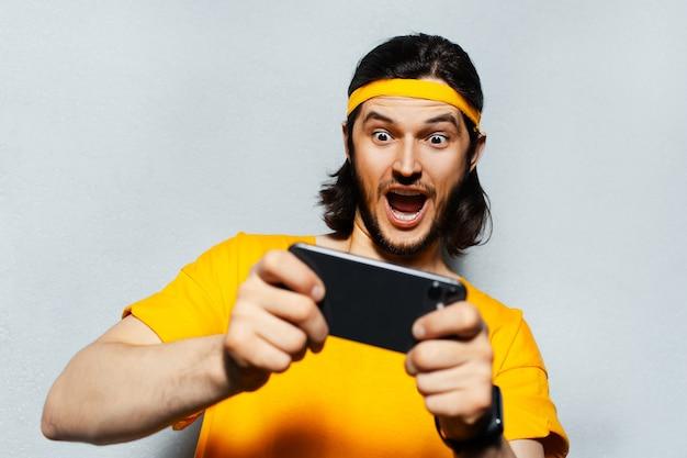 Studioportret van de jonge verraste mens met lang haar, speelspel op smartphone op grijze geweven achtergrond; het dragen van gele band voor hoofd en shirt.
