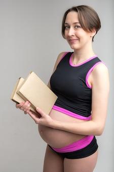 Studioportret van de jonge volwassen zwangere stapel van de vrouwenholding boeken, die voor babybirthconcept, witte muur voorbereidingen treffen