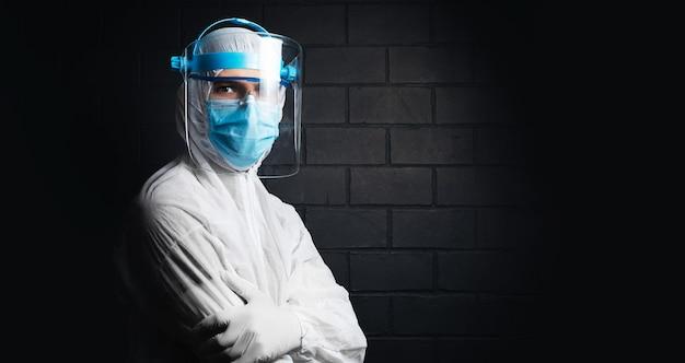 Studioportret van een arts die een pbm-pak draagt tegen coronavirus en covid-19, op de achtergrond van een zwarte bakstenen muur. pandemisch concept.