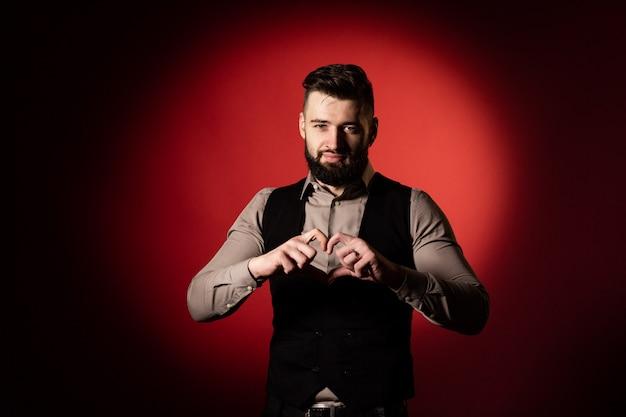 Studioportret van een bebaarde man in een vest op een rode achtergrond. de man vouwde zijn vingers in de vorm van een hart