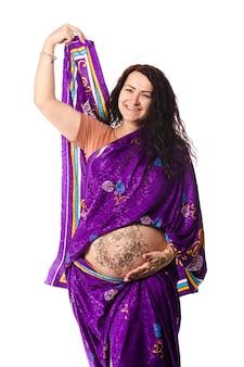 Studioportret van een gelukkige zwangere vrouw in indiase sari, een zwangere buik beschilderd met henna