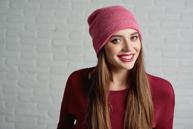 Studioportret van een jong glimlachend model, dragend roze glb en rode sweatshot.