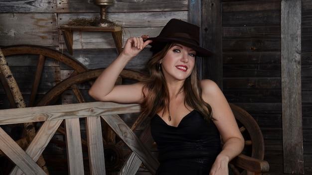 Studioportret van een jonge brunette van europese afkomst, in een zwarte jumpsuit en hoed. een slanke vrouw in zwarte kleding en een hoed zit tegen de achtergrond van een rustiek interieur