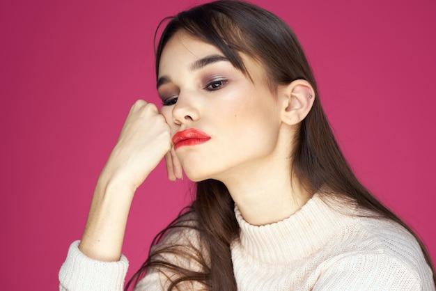 Studioportret van een jonge mooie vrouw met rode lippenstift op lippen, roze