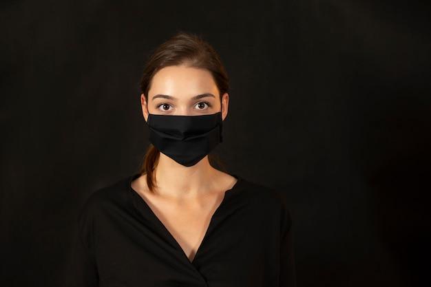 Studioportret van een jonge vrouw die een gezichtsmasker op donkere achtergrond draagt.