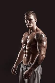 Studioportret van een shirtless atletisch getatoeëerd mannetje