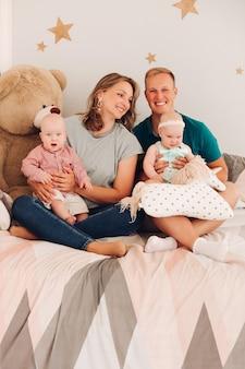 Studioportret van een vrolijk gezin met twee baby's op het bed. gelukkig lachende moeder en vader met dochter en zoon zittend op een gezellig bed met pluchen speelgoed.