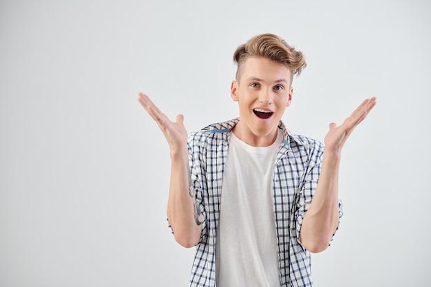 Studioportret van gelukkige opgewekte of geschokte tiener die mond opent en wapens opheft