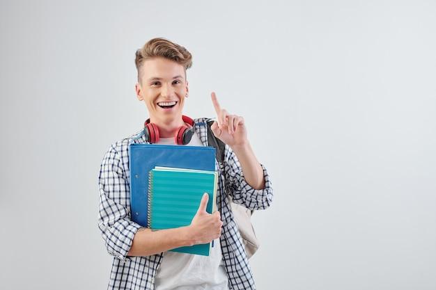 Studioportret van gelukkige opgewekte tienerjongen met studentenboeken in hand die in de lucht benadrukken en glimlachen
