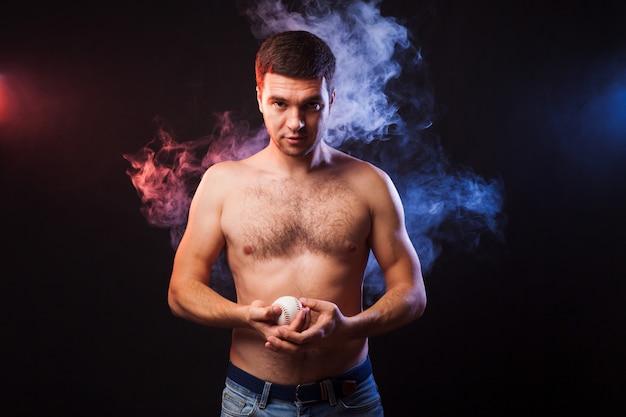 Studioportret van gespierde sportman met speler het stellen op zwarte achtergrond in gekleurde rook met honkbal in zijn hand.