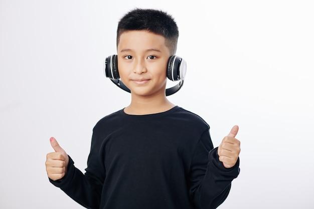 Studioportret van glimlachende vietnamese jongen in hoofdtelefoons die aan muziek luisteren en thumbs-up tonen