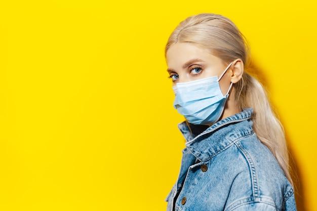 Studioportret van jong blond meisje met blauwe ogen, dat medisch gezichtsmasker draagt tegen coronavirus. achtergrond van gele kleur.