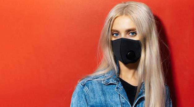 Studioportret van jong blond meisje met blauwe ogen die ademhalingsgezichtsmasker dragen tegen coronavirus. achtergrond van rode kleur met exemplaarruimte.