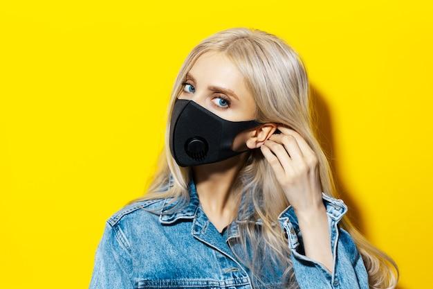 Studioportret van jong blond meisje met blauwe ogen, het opzetten van een ademhalingsmasker van zwarte kleur, tegen coronavirus. achtergrond van gele kleur.