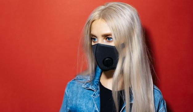 Studioportret van jong blondemeisje die ademhalingsgezichtsmasker dragen tegen coronavirus op rode kleur met exemplaarruimte.