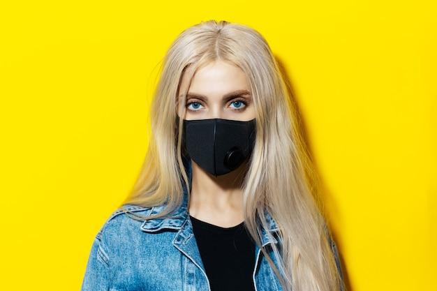Studioportret van jong blondemeisje die zwart medisch ademhalingsmasker dragen tegen coronavirus. achtergrond van gele kleur.