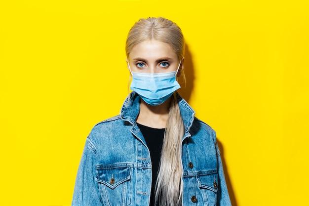 Studioportret van jong blondemeisje in spijkerjasje die medisch gezichtsmasker dragen tegen coronavirus op gele achtergrond.