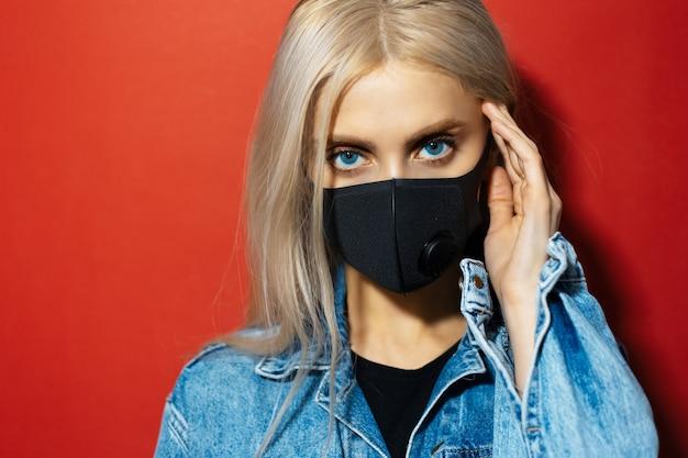 Studioportret van jong blondemeisje met blauwe ogen in spijkerjasje die medisch gezichtsmasker dragen tegen coronavirus op rode achtergrond.