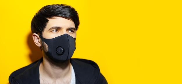 Studioportret van jonge kerel die zwart ademhalingsgezichtsmasker draagt tegen coronavirus op gele achtergrond met exemplaarruimte.