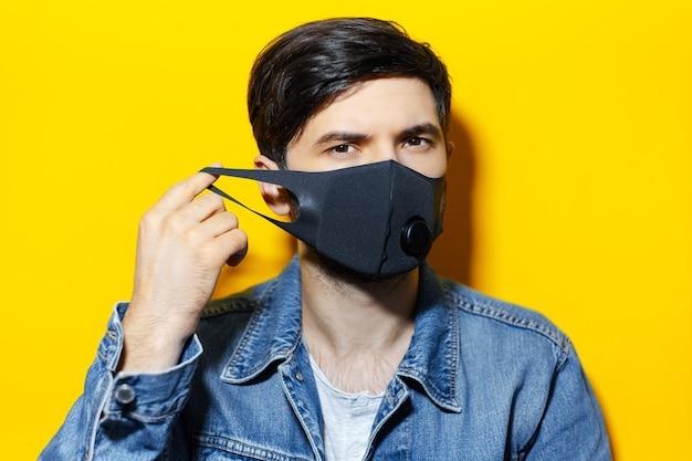 Studioportret van jonge kerel, die zwart ademhalingsgezichtsmasker opzet tegen coronavirus, achtergrond van gele kleur.