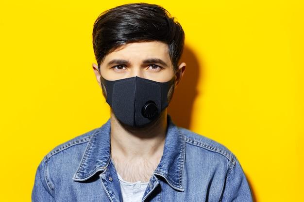 Studioportret van jonge kerel in spijkerjasje die ademhalings medisch masker op gezicht van zwarte kleur dragen. coronavirus preventie. achtergrond van gele kleur.