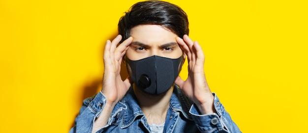 Studioportret van jonge kerel met handen op het hoofd, die zwart ademhalingsmasker dragen tegen coronavirus. achtergrond van gele kleur.