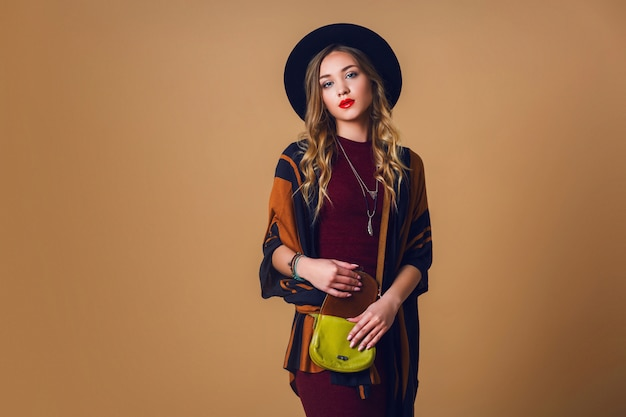 Studioportret van jonge verse blondevrouw in bruine stroponcho, wol zwarte trendy hoed en ronde glazen die camera bekijken. groen leer had tas.