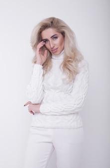 Studioportret van mooie langharige blondevrouw in hete sweater op witte achtergrond