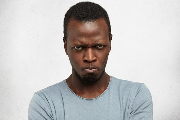 Studioportret van ontevreden, boos, knorrig en pissig jonge afro-amerikaanse man