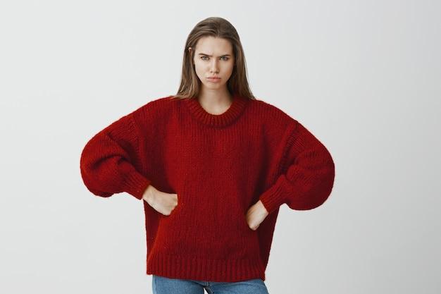 Studioportret van ontheemde boze blanke vriendin in rode losse trui, hand in hand op heupen en fronsen, beledigd voelen, afkeer en teleurstelling uiten, mokkend op vriendje