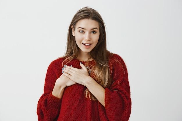 Studioportret van tevreden gevleid jonge aantrekkelijke vrouw in rode losse sweater, met palmen op borst en breed glimlachend, sprekend met vriend die in liefde bekent