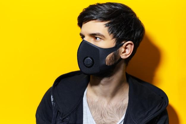 Studioprofielportret van jonge kerel die ademhalingsgezichtsmasker van zwarte kleur draagt, tegen coronavirus. achtergrond van gele kleur.