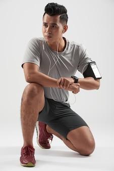 Studioschot van aziatische jonge en sportman die knielend zijn apparaten dragen stellen